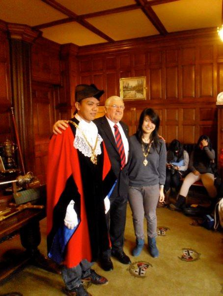 Mr. Harold trying on a British traditional costume with Mayor Layland and a Binusian.